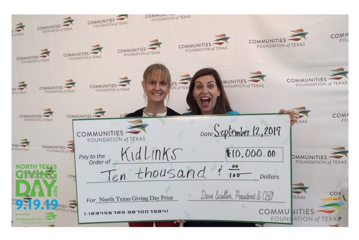 Two women hold a large check made out to KidLinks for $10,000